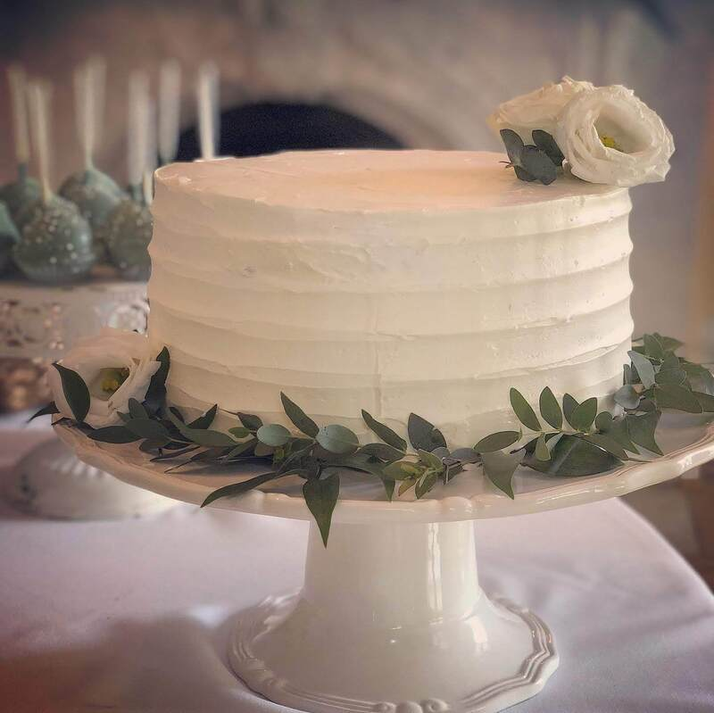 Simple elegant bridal shower cake with greenery and flowers