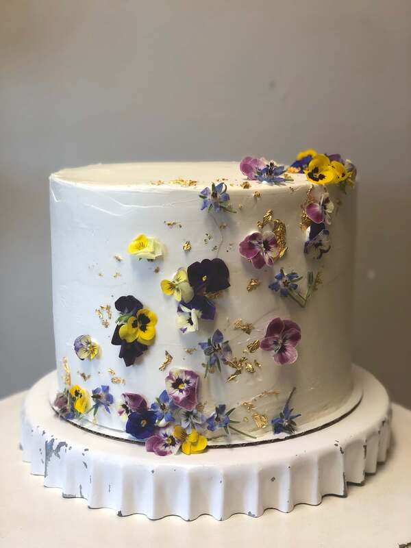 1 tier bridal shower cake covered in edible flowers and gold leaf
