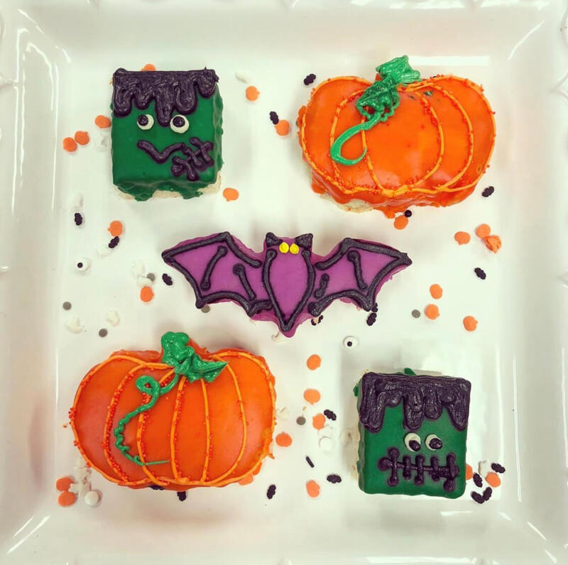 Halloween themed petit four desserts in the shape of bats and pumpkins